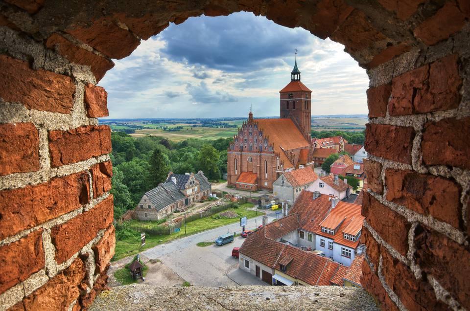 Vista de la antigua iglesia a través de la ventana de la torre del castillo, Reszel, Warmia, Polonia