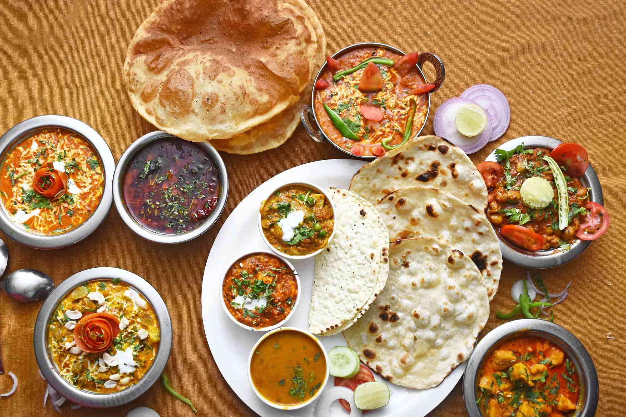 full spread of Indian dishes on a brown table cloth