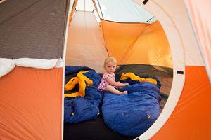 Little girl sitting on sleeping bag inside a tent.