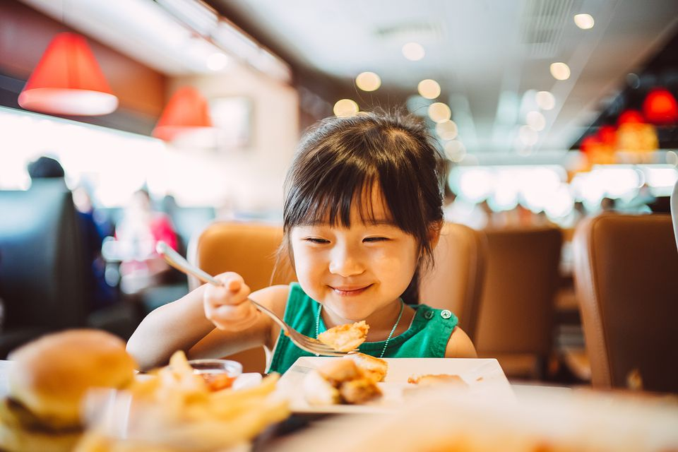 Young Asian girl eating at a restaurant