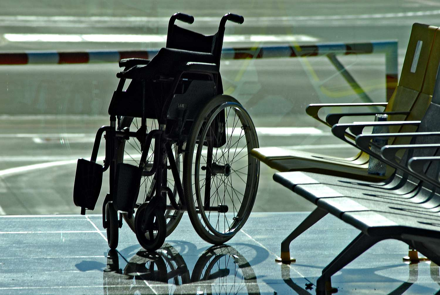 Wheelchair By Chairs At Airport Departure Area